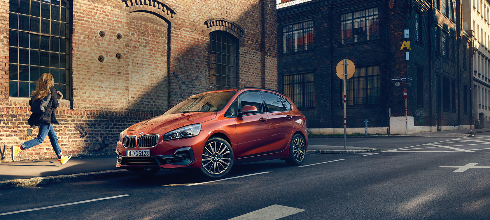 BMW 2 Series Active Tourer F45 Sunset Orange metallic three-quarter front view parking on the road